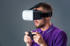 Man in studio wearing virtual reality headset playing game. Man dressed in a purple T-shirt royalty free stock images