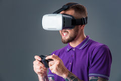 Man in studio wearing virtual reality headset playing game. Man dressed in a purple T-shirt royalty free stock photography