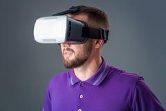 Man in studio wearing virtual reality headset playing game. Man dressed in a purple T-shirt stock image