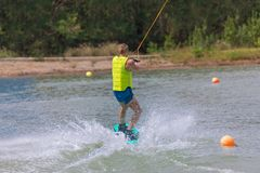 Man study wakeboarding on a blue lake. Summer sports Stock Photography