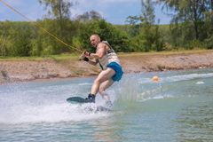 Man study wakeboarding on a blue lake. Summer sports Royalty Free Stock Image