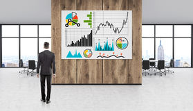 Man studying graphs. Man standing in New York office studying charts on large horizontal poster. Concept of business development and promotion. 3d rendering Royalty Free Stock Images