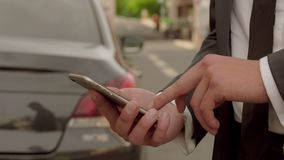 Man studying information on mobile phone on background of car. Man in suit studying information on mobile phone on background of car stock video