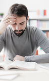 Man studying at the library. Adult focused man sitting at desk and studying at the library, learning and self improvement concept Royalty Free Stock Image
