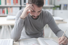 Man studying at the library. Adult focused man sitting at desk and studying at the library, learning and self improvement concept stock images