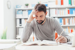 Man studying at the library. Adult focused man sitting at desk and studying at the library, learning and self improvement concept royalty free stock images