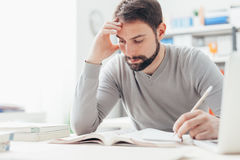 Man studying at the library. Adult focused man sitting at desk and studying at the library, learning and self improvement concept stock photography