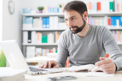 Man studying in the office. Young handsome man sitting at office desk, studying a book and connecting to internet using a laptop Stock Photos