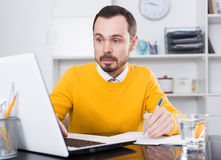 Man studying at online courses. Male student having a productive day at online courses at home Royalty Free Stock Photos