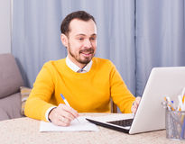 Man studying at online courses. Young male student studying at online courses productively at home Stock Image