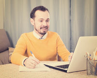 Man studying at online courses. Young male student studying at online courses productively at home Stock Photos