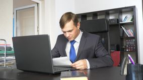 A man is studying a paper document. Sitting in the office royalty free stock photography