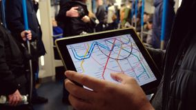 Man studying a subway map on a tablet computer riding at underground. Moscow, Russia - February 11, 2018: Man studying a subway map on a tablet computer riding stock video
