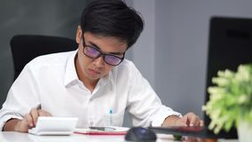 Man studying and using calculator. Young man studying and using calculator stock footage
