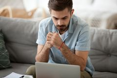 Man studying using computer reading message online. Serous millennial male sitting on couch at home and looking at computer screen reading message email. Student stock images