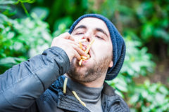 Man stuffing his face with french fries. Blurred romantic background Royalty Free Stock Photo