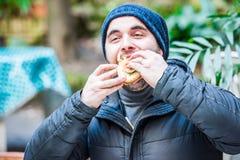 Man stuffing his face with a hamburger. Man stuffing his face with hamburger - blurred romantic background Royalty Free Stock Image