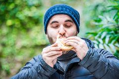 Man stuffing his face with a hamburger and feeling nice Royalty Free Stock Image