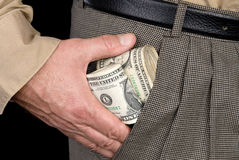 Man stuffing wads of cash into his pocket. A man stuffs wads of cash into his pocket Royalty Free Stock Photos