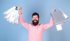 Man with stylish beard and mustache carrying shopping bags. Winner of luxury boutique gift certificate isolated on blue. Background. Bearded man in pink shirt stock photo