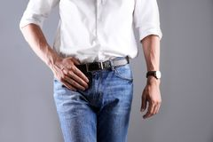 Man in stylish blue jeans. On grey background stock photography