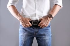Man in stylish blue jeans. On grey background stock image