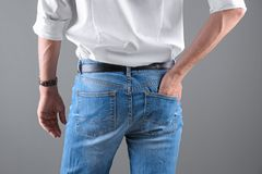 Man in stylish blue jeans. On grey background royalty free stock photo