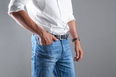 Man in stylish blue jeans. On grey background royalty free stock photos