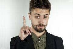 Man in stylish clothes held up an index finger. Attractive unshaven young man in stylish attire raised his index finger and stares with raised eyebrows Stock Photos