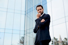A man in a stylish dark suit standing on the background of the business center Royalty Free Stock Photography