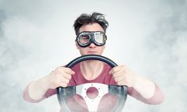 Man in stylish goggles with steering wheel on background, car driver concept Royalty Free Stock Photos