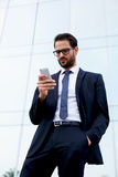 Man in a stylish suit went on a break and reading messages on mobolnom Stock Image