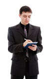 Man in a suan entry in a notebooit, makes. A young man in a suit, makes an entry in a notebook, isolated on a white background Stock Image