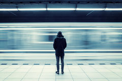 Man at subway station. Lonely young man shot from behind at subway station with blurry moving train in background Royalty Free Stock Photo