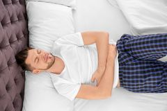 Man suffering from abdominal pain. In bedroom Royalty Free Stock Photography
