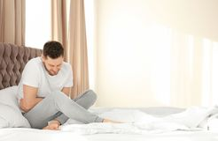 Man suffering from abdominal pain. In bedroom Royalty Free Stock Image