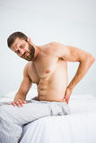 Man suffering from back pain on bed Royalty Free Stock Images