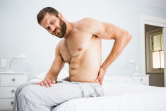Man suffering from back pain on bed Royalty Free Stock Photos