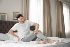 Man suffering from back pain. In bedroom Royalty Free Stock Photography