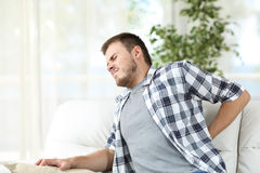 Man suffering back pain at home. Unhappy man suffering back pain sitting on a sofa in the living room at home Stock Image