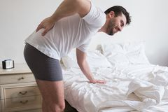 Man awakening in the morning and suffering backache Royalty Free Stock Photos