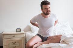Young man with back pain sitting on bed in his room Royalty Free Stock Photography