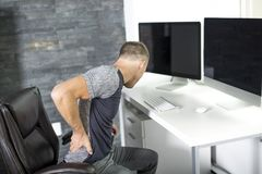Man suffering from backache while sitting at computer desk in office Royalty Free Stock Image