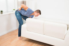 Man Suffering From Backpain While Lifting Sofa Royalty Free Stock Photography