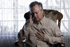 Man Suffering with Chest and Head Pains. Older man sitting in a rocking chair and wincing while holding his chest and head Royalty Free Stock Images