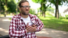 Man suffering chest pain, sitting outdoors, heart arrhythmia, ischemic disease. Stock photo stock photo