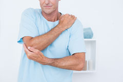 Man suffering from elbow pain. In medical office Stock Photography