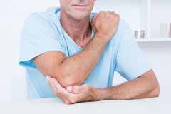 Man suffering from elbow pain. In medical office Royalty Free Stock Image