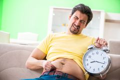 The man suffering from extra kilos in time management concept. Man suffering from extra kilos in time management concept royalty free stock photo