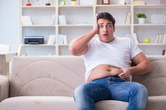 The man suffering from extra weight in diet concept. Man suffering from extra weight in diet concept Royalty Free Stock Image